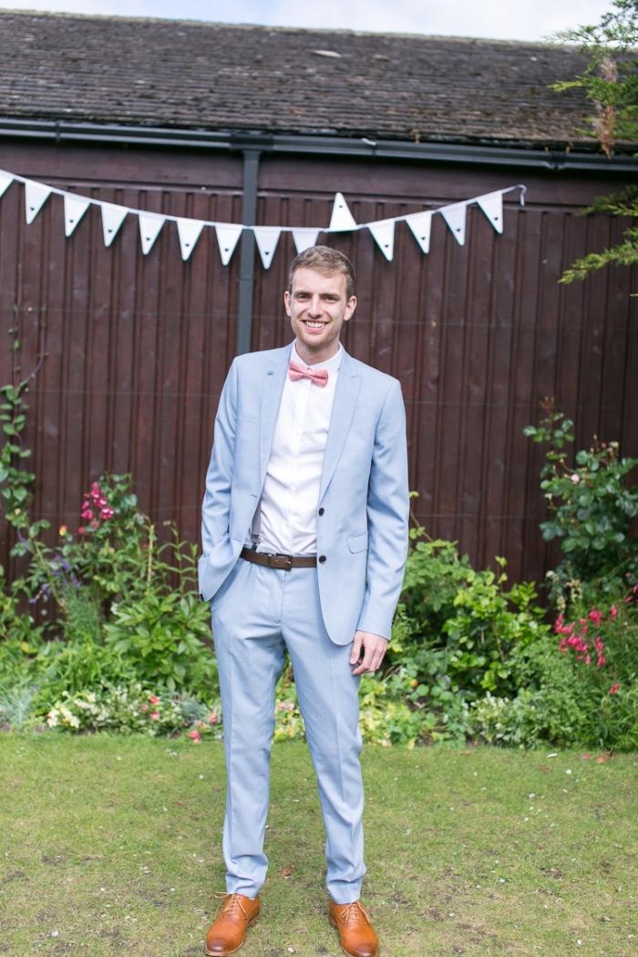 look à la fois chic et décontracté en costard mariage en bleu clair assorti avec un noeud papillon rose et des chaussures oxford