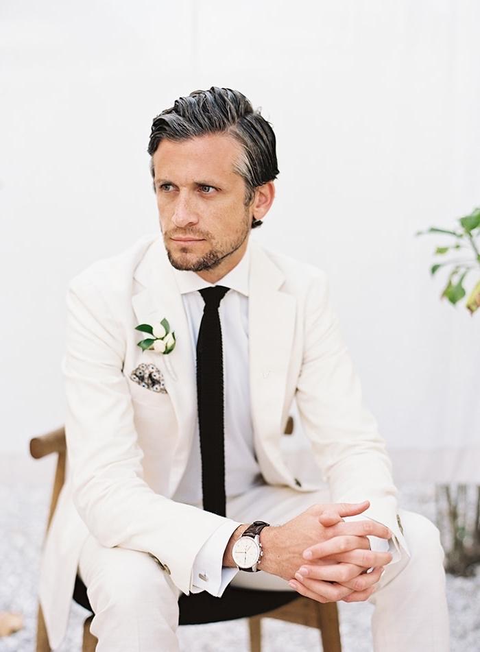 vision élégante et moderne en ton sur ton avec un costume marié blanc cassé associé à une chemise blanc immaculé, le tout magnifié par une cravate slim noir
