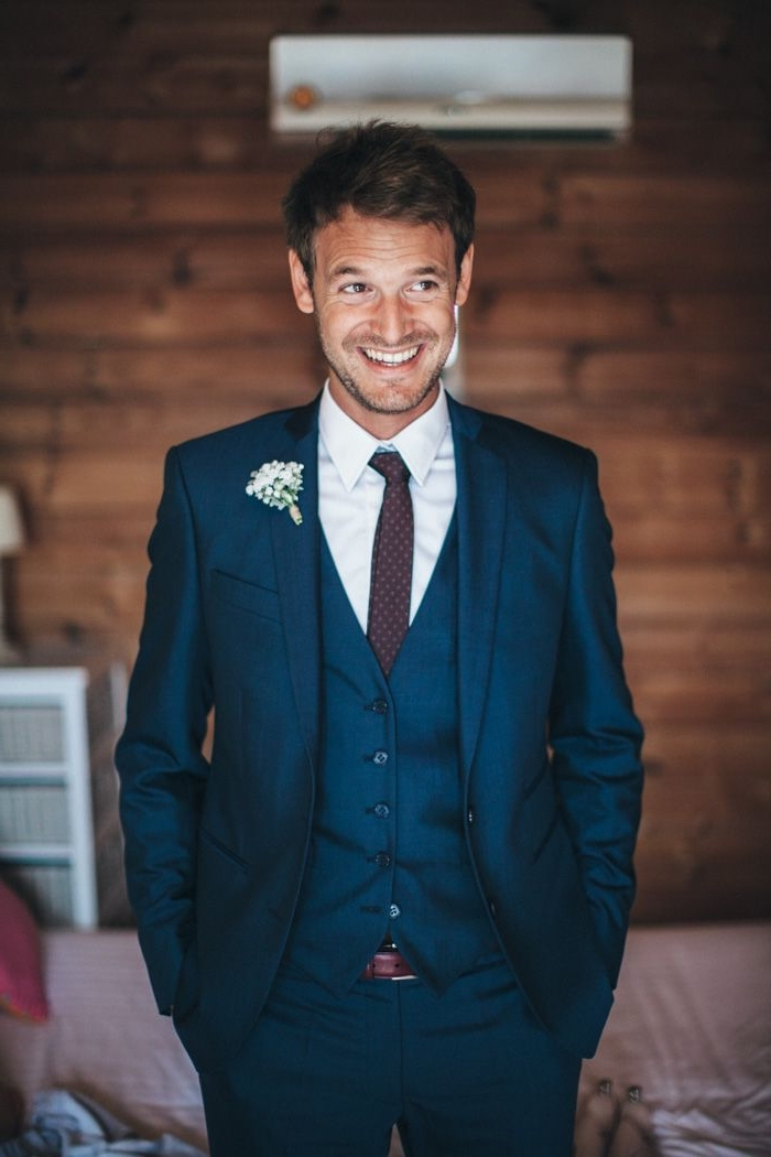 un costume homme pas cher e couleur bleu canard profond avec gilet ajusté et une cravate bordeaux assortie avec la ceinture