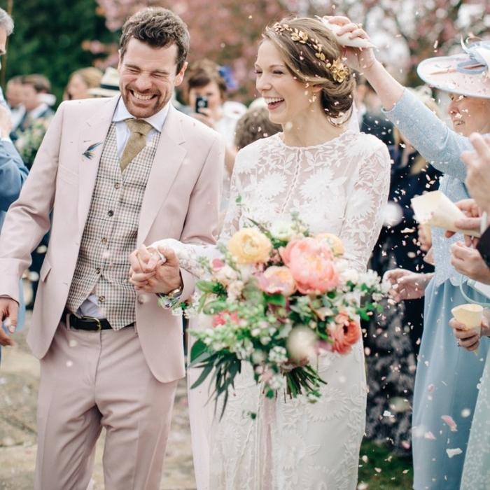 un costume marié de trois pièces en nuance très douce du rose pastel assorti avec des accessoires dans les tons beige et marron