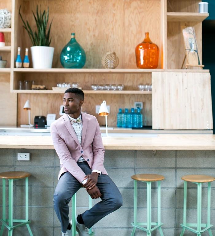 costard mariage dépareillé qui casse les codes vestimentaires pour un look chic et moderne, pantalon gris associé à une veste rose pastel, le tout complété par un noeud papillon imprimé