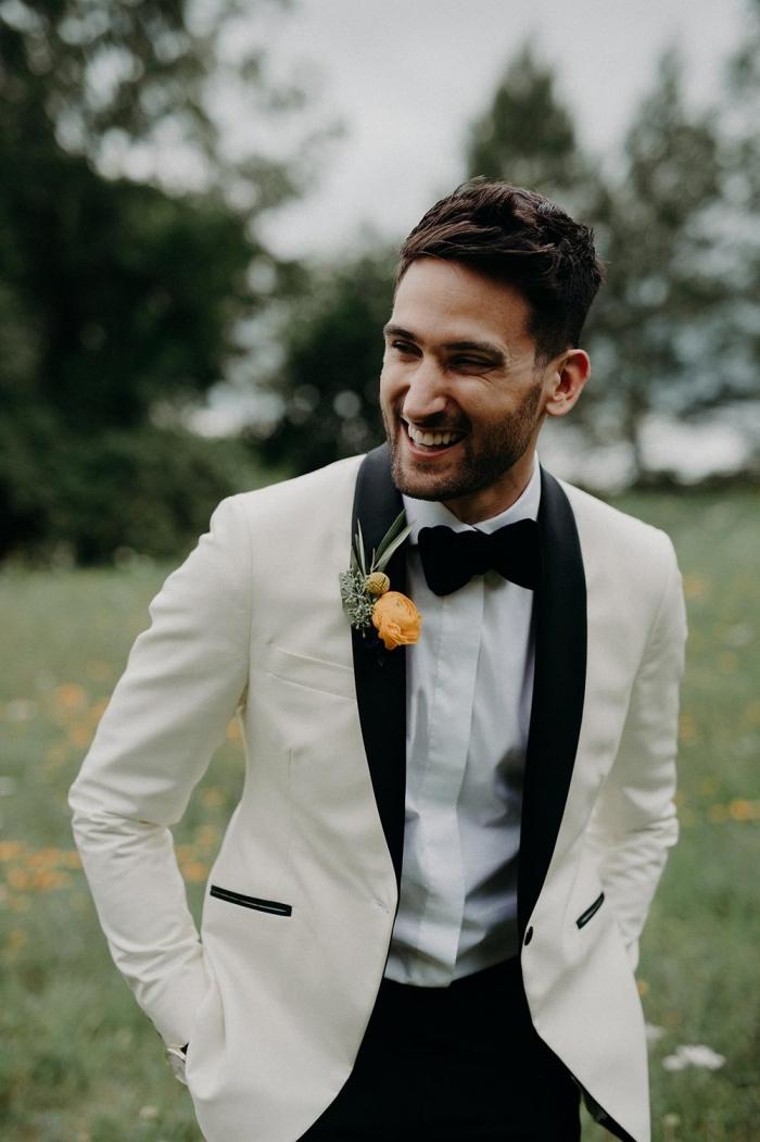 look élégant et atemporel en smoking de mariage blanc et noir avec une veste à revers et à poches droites contrastés