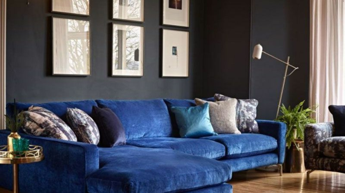 grand canapé bleu, coussins déco, petite table en matière argentée, peinture murale sombre