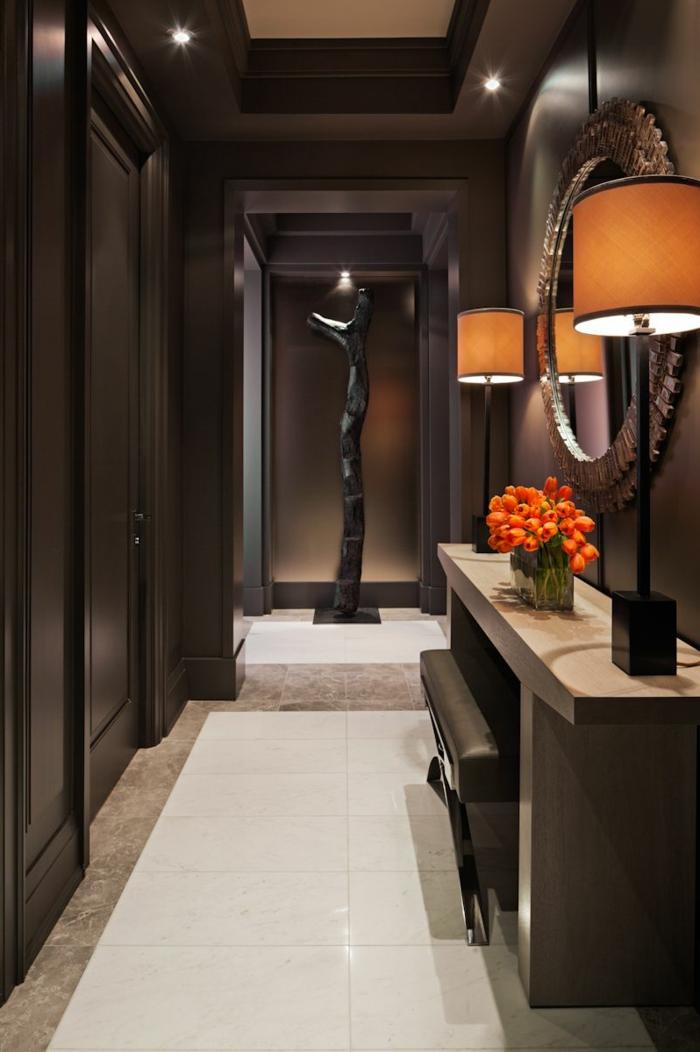 couloir long, console d'entrée imposante, miroir rond encadré, sculpture noire, lampes abat-jour