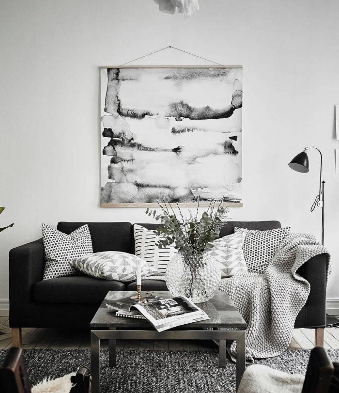 esprit minimaliste avec objets décoratifs en blanc et noir pour une ambiance cozy, déco de salon aux murs blancs avec meubles et accessoires gris