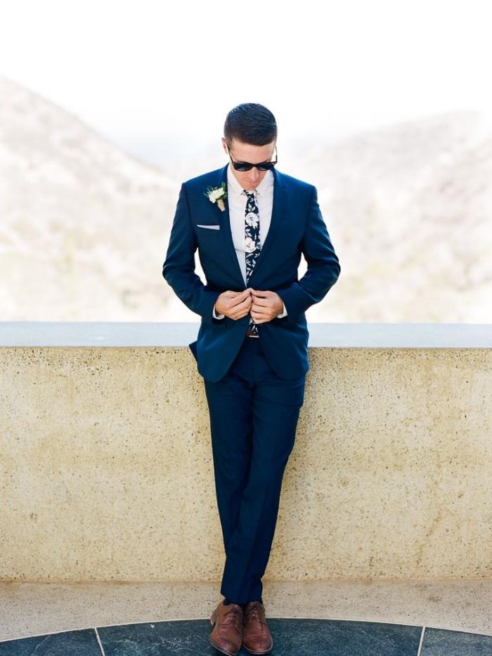 un costume bleu marine bien taillé decoupe moderne combiné avec une cravate imprimé floral d'esprit seventies, silhouette élégante en tenue homme mariage sur-mesure