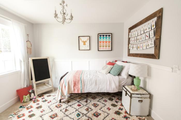 peinture chambre fille, déco chambre fille ado, comment décorer sa chambre, panneau en bois avec des messages colorés au-dessus du lit, tapis en style ethnique aux losanges colorés, lustre baroque avec des ampoules en forme de chandelles, tableau noir en bois, malle blanche