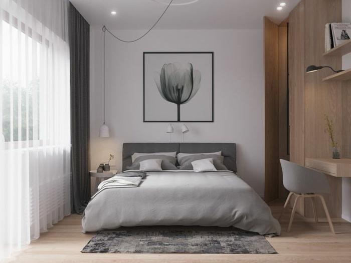tapis usé, tête de lit grise, cadre peinture abstraite, spots encastrés et lampe suspendue, chaise scandinave près d'un bureau suspendu en bois avec étagère