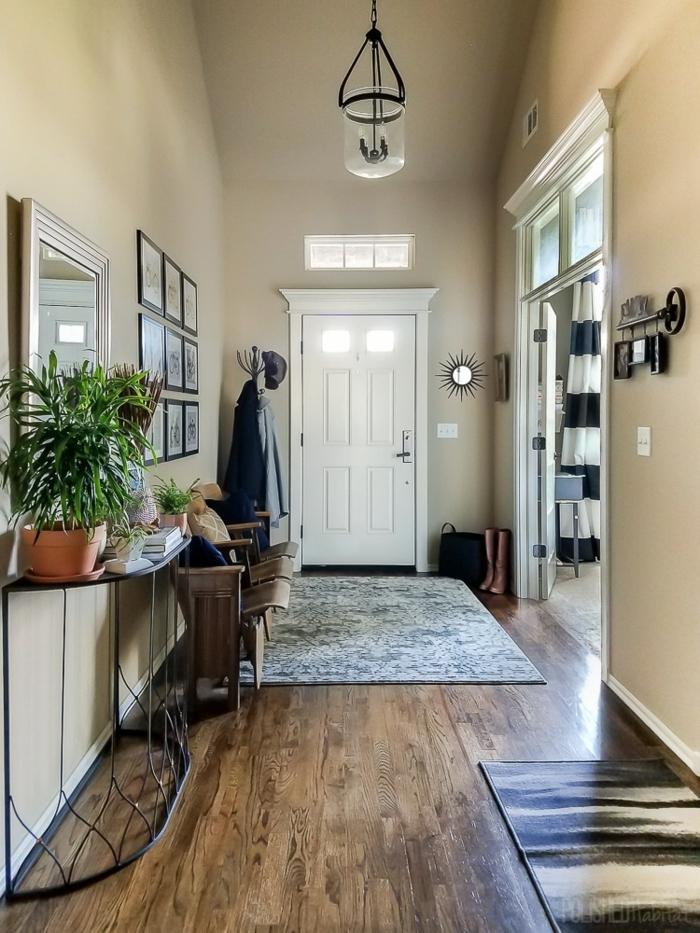 jolie entrée avec le sol en bois, tapis gris, chaises vintage, console noire avec des pots de fleurs, miroir encadré blanc, peinture beige taupe