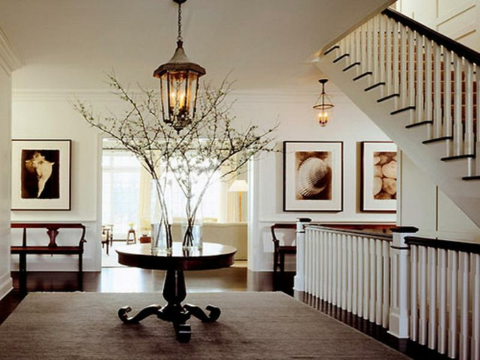 petite table ronde, tapis taupe, escalier avec rambarde blanche, luminaire lanterne, créer une entrée dans un espace ouvert