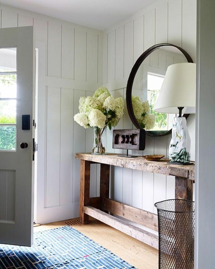 miroir entrée rond encadré, lambris mural blanc, bouquet de pivoines, table en bois brut