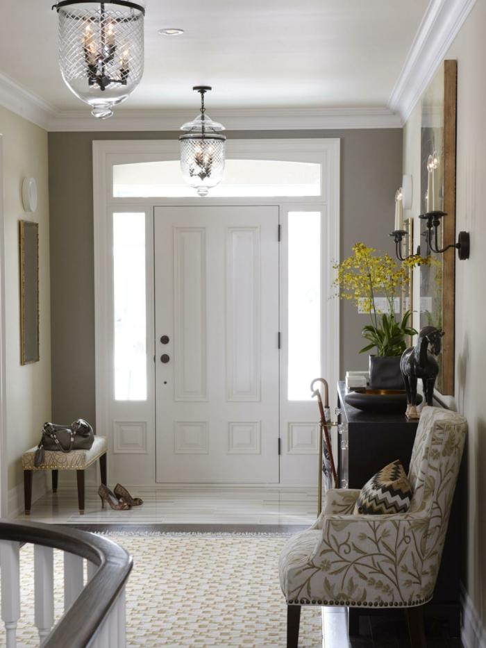 petit tabouret dans une entrée blanche, fauteuil à motifs floraux, luminaire lanterne