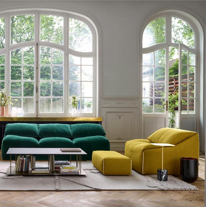 grandes fenêtres arcs dans un salon spacieux à l'équipement minimaliste, sofa vert et canapé jaune avec tabouret