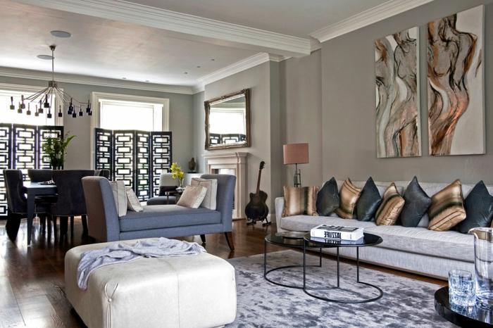 grand pouf blanc, tapis gris, petite table basse, canapé gris, plusieurs coussins déco, tableau avec peinture