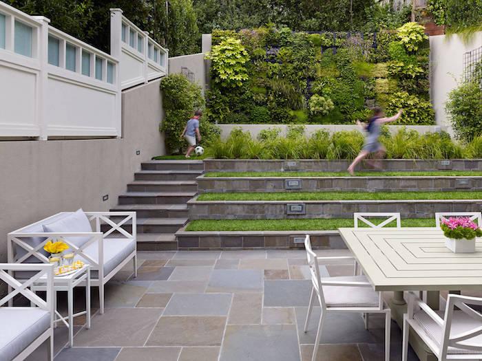améangement cour extérieur avec revetement dalles de pierre, bancs, table et chaises salle à manger extérieure, mur végétal extérieur, jardin en pente