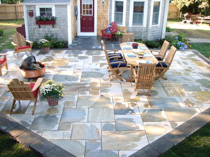terrasse devant maison avec revêtement sol en dalles de béton, salle à manger extérieure en chaises et table de bois, petit barbecue, gazon vert
