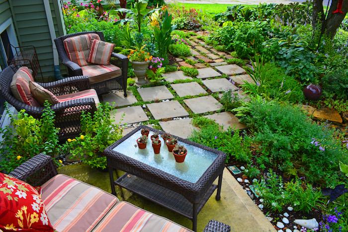 chemin de dealles de béton, plusieurs arbustes bas, table et fauteuils en rotin, aménagement de jardin terrasse original