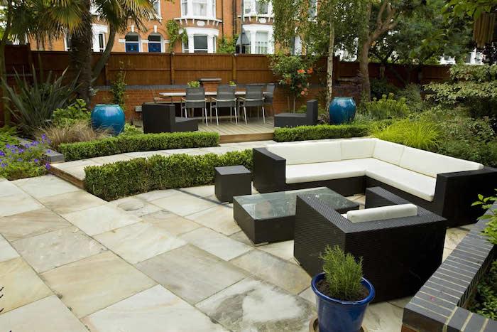 décoration terrasse recouverte de dalles, canapé, table et fauteuil, bordures de buis, coin salle à manger exterieur