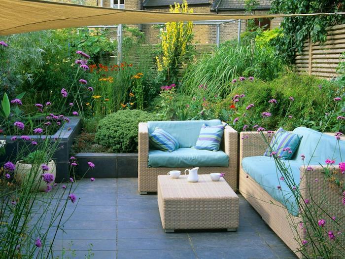 décoration terrasse revetement de dalles, canapé et fauteuil en rotin, table basse rotin, jardin à l anglaise avec arbustes, arbres et fleurs