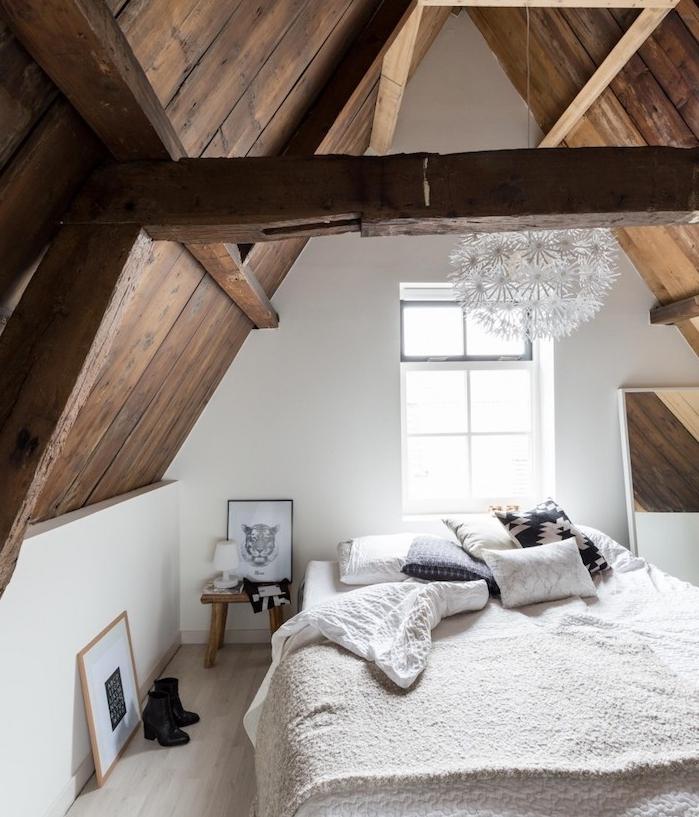 modèle déco chambre sous comble avec ossature bois, linge de lit gris et blanc, parquet bois clair, suspension blanche originale, miroir rectangulaire, deco artistique noir et blanc