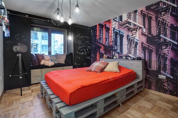 papier peint new york, lampe industrielle, mur en peinture tableau noir, lit en palette grise, matelas rouge, parquet bois clair, suspensions industrielles