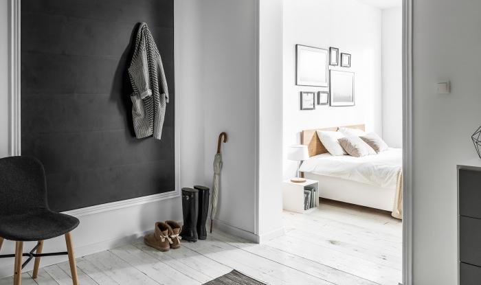 esprit minimaliste dans un couloir et chambre à coucher aux murs blancs et parquet de bois clair avec pan de mur gris foncé