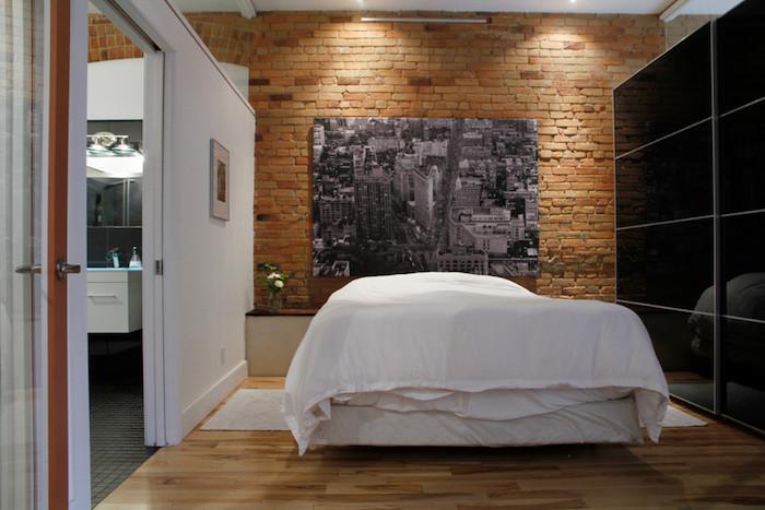 exemple de décor industriel avec mur de briques, panneau décoratif noir et blanc, style new york, linge de lit blanc, armoire noire