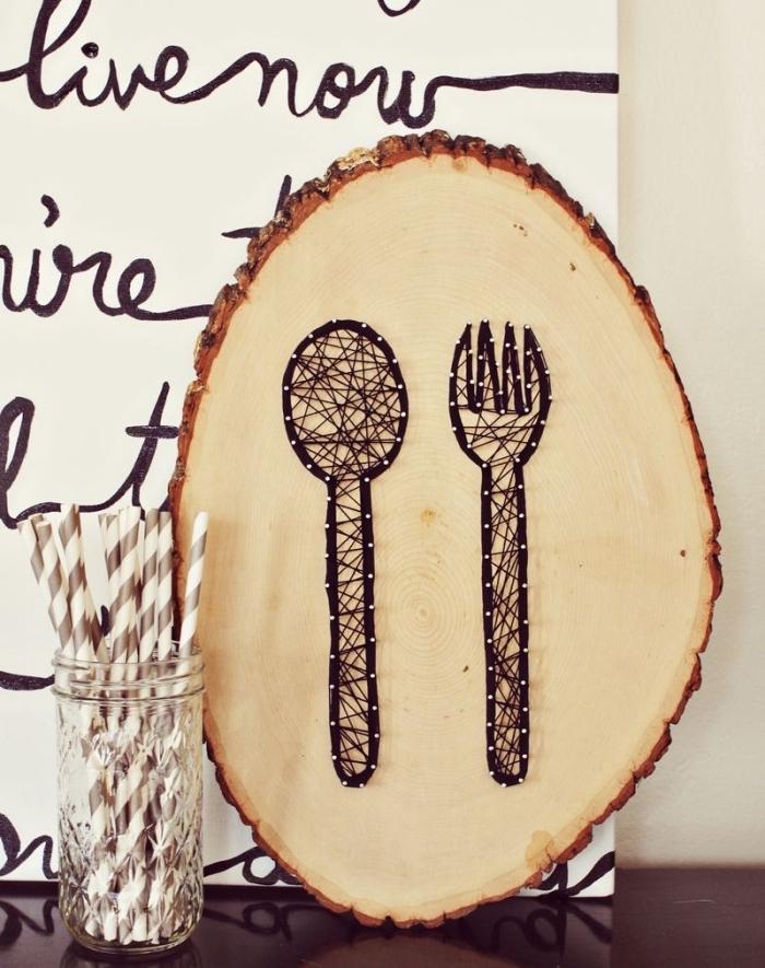 aménagement coin de cuisine avec panneau blanc à lettres noires et un tableau de bois à dessins cuillère et fourchette