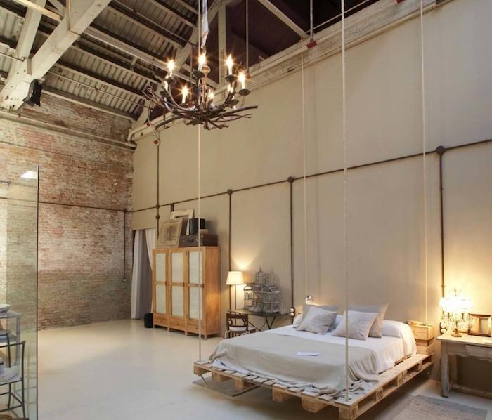 deco industrielle chic dans un loft, lit en palette suspendu, armoire industrielle de bois, lustre baroque, ossature apaprente