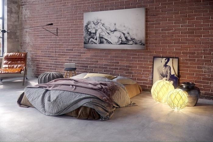 chaise style industriel dans une chambre décorée de briques, matelas à même le sol avec linge de lit pastel, deco murale graphique, boules blanches lumineuses