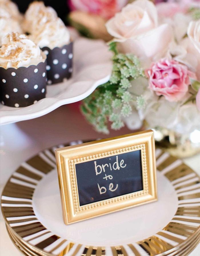 deco de table mariage en cadre or avec nom mariée écrit sur un fond peinture tableau noir avec lettres or, assiettes blanches et or, cupcakes