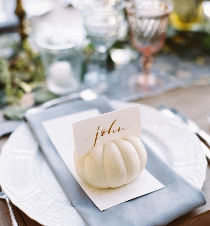 petite citrouille avec étiquette blanche nom écrit en lettres or calligraphie, assiette blanche, serviette gris, centre de table floral