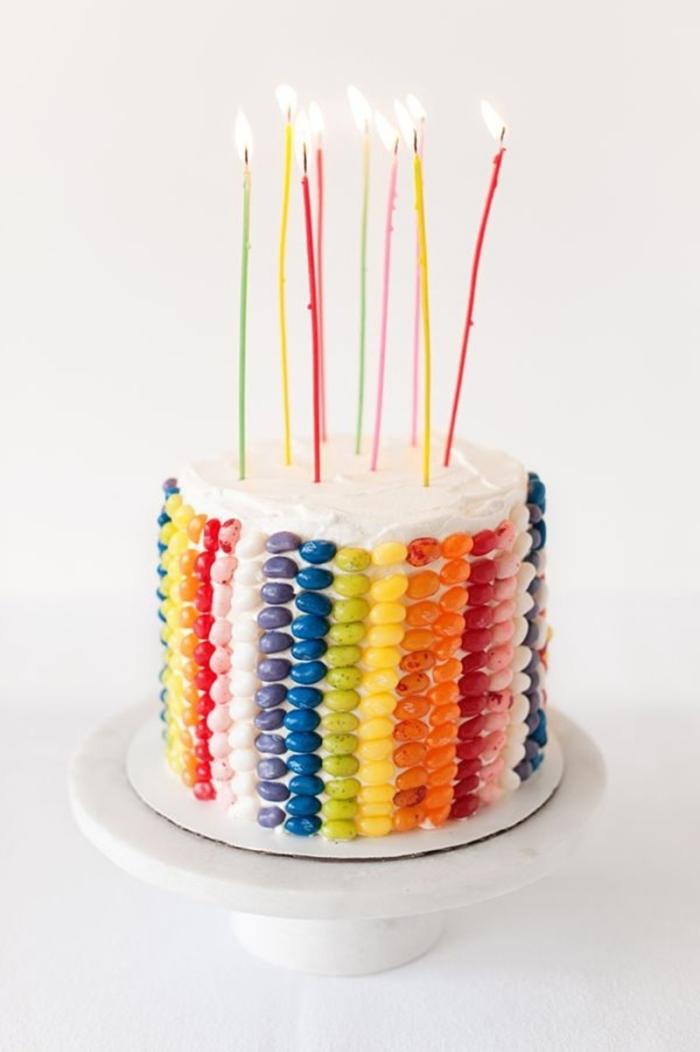 recette de gateau cake arc-en-ciel nappé de crème au beurre et décoré de bonbons haricots gélifiés sur les côtés