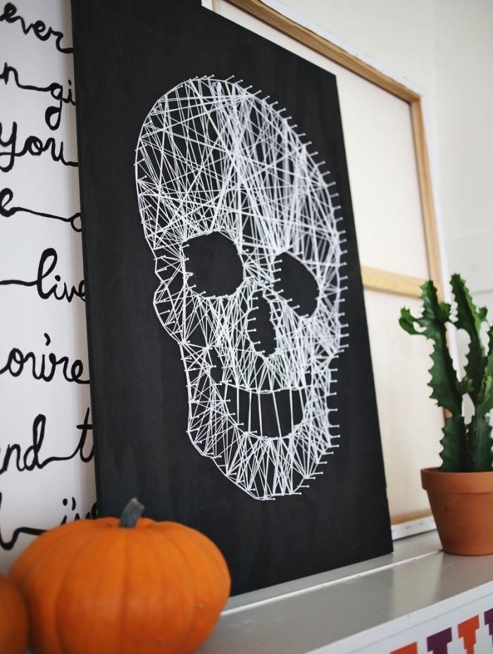 exemple de déco de Halloween DIY avec un tableau noir à fil blanc en forme de crâne et une petite citrouille orange