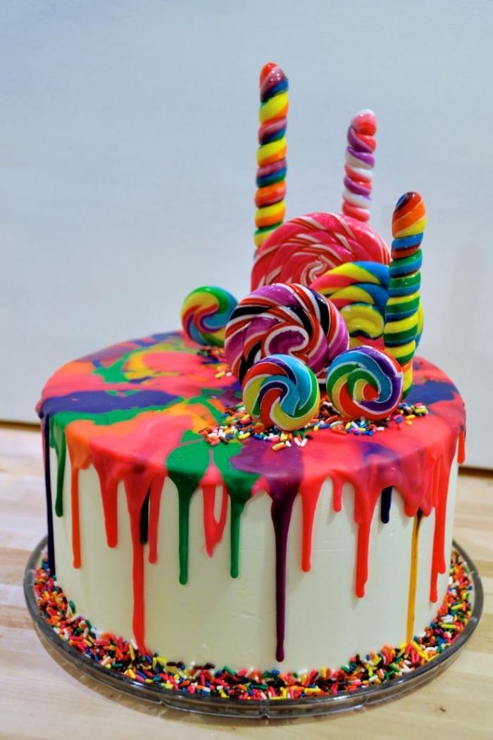 idée pour un gateau cake design original au glaçage coulant arc-en-ciel décoré avec des sucettes colorées