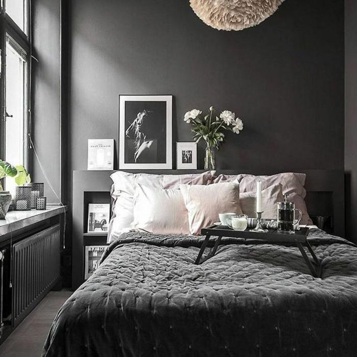 chambre à coucher en gris et blanc, coussins blancs, plafonnier rond, petites plantes vertes, photographies artistiques