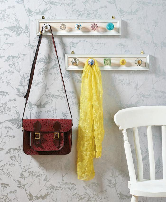 petits cadres rectangulaires boisés avec des boutons de porte en guise d'accroche manteaux, écharpe jaune et sac à main femme