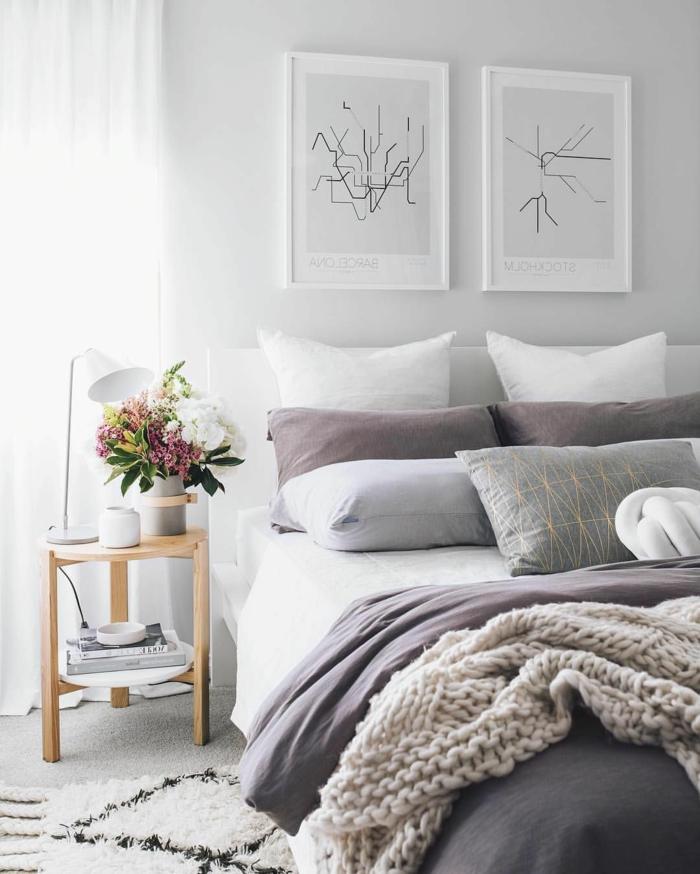 chambre scandinave, lit en blanc et gris, petit chevet en bois, tapis blanc, deux peintures abstraites, deco chambre moderne
