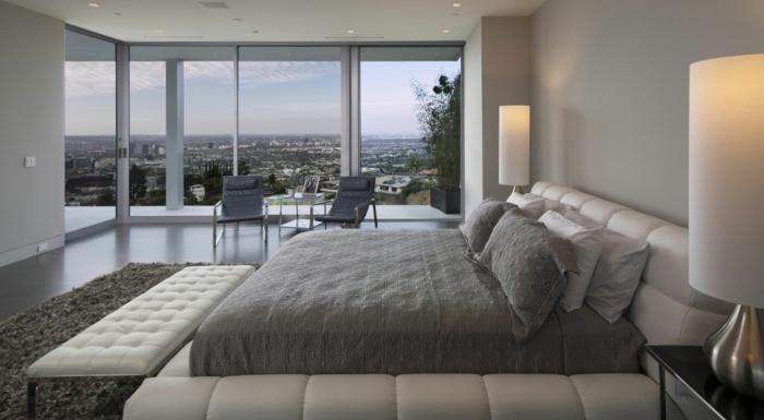 chambre de luxe avec vue, lampes cylindiques, banquette de lit blanche, tapis gris anthracite, murs gris