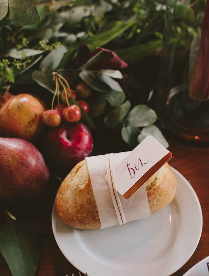 assiette avec un pain de campagne avec étiquette prénom invité, centre de table mariage automne en fruits et feuillage vert