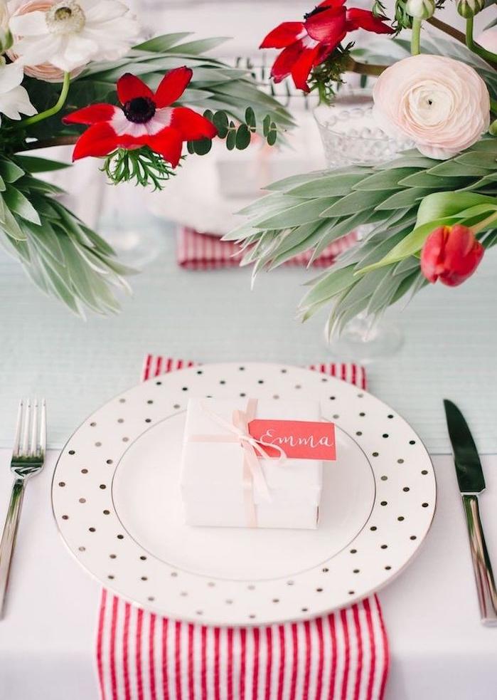 un petit cadeau surprise dans une boite blanche avec étiquette rose comme porte nom mariage, centre de table en bouquets de fleurs et serviettes à rayures