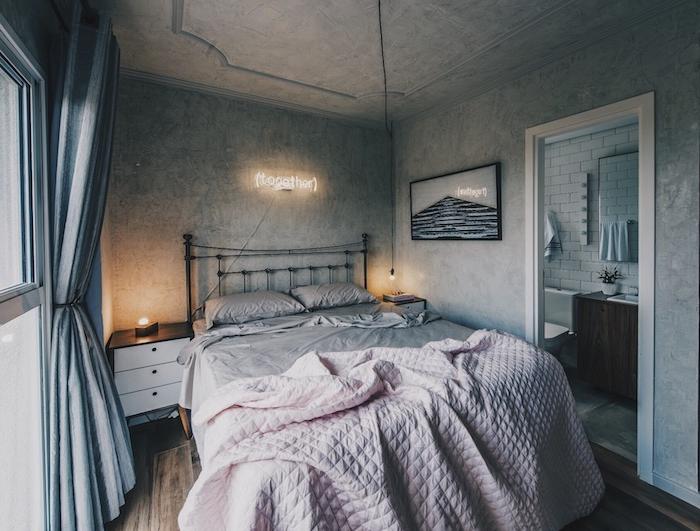 exemple de deco murale industrielle de lettres lumineuses, cadre noir et gris, linge de lit rose et gris sur un lit metallique noir, parquet bois, murs gris
