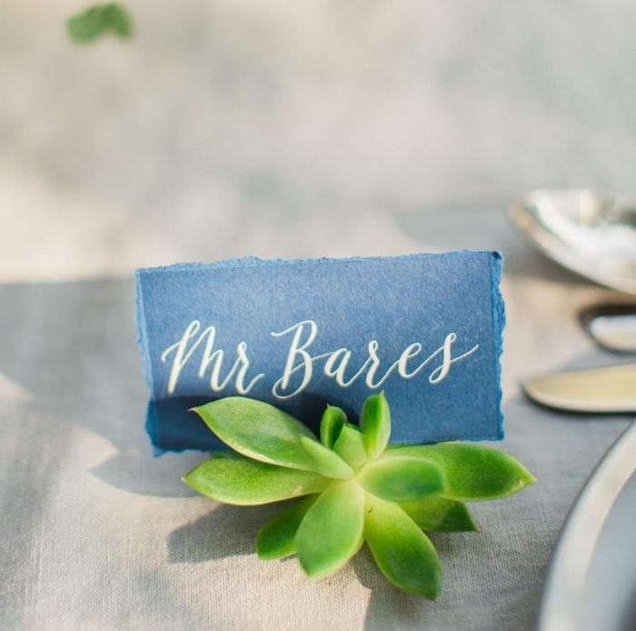 porte nom de table en fleur succulent avec étiquette en tissu noir et lettres nom invité blanches, nappe en toile de bache