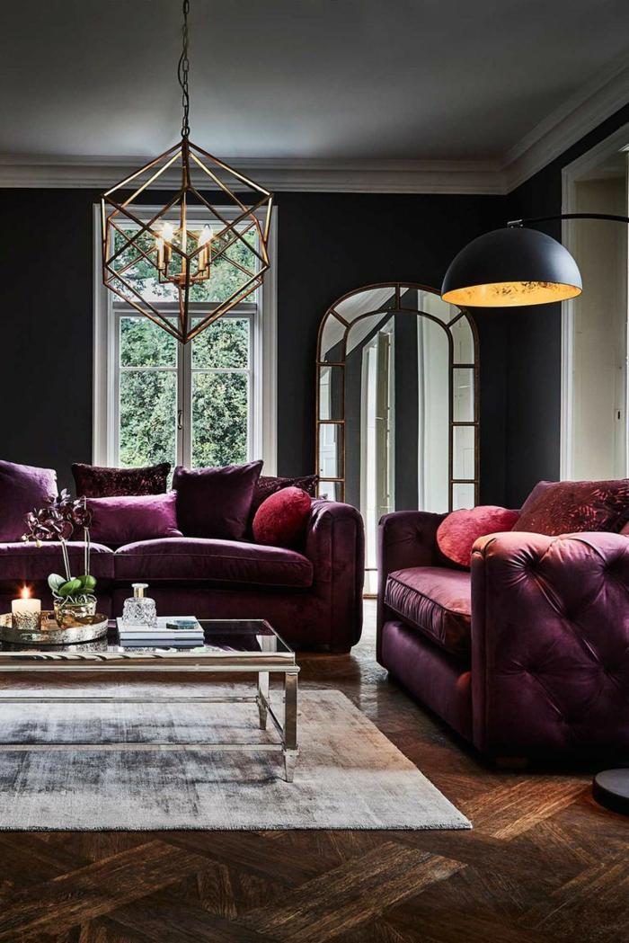 salon cocoon en gris et pourpre, table basse en verre et métal doré, grands sofas pourpres, lampe pendante usine, plafonnier géométrique