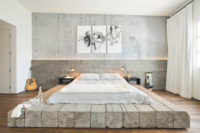 murs effet beton dans une chambre à coucher loft industriel, matelas gris clair sur une base en poutres de bois grises, deco murale en panneaux noir et blanc