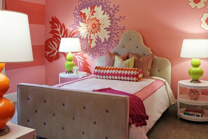 murs en couleur saumon, rouge et blanc pour une déco chambre fille ado relaxante, deux luminaires design avec base orange et base vert pomme avec des abat-jours en blanc, lit avec deux bouts matelassés, table ronde blanche a trois niveaux