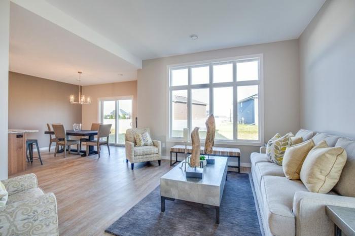 table basse blanche, tapis bleu, sol stratifié, sofa gris clair, coussins beiges, peinture blanche