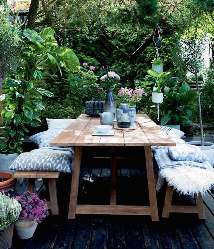bancs bois et table en bois brut sur une terrasse bois brut, jardin envahi par une végétation verte, bouquets de fleurs champetre, plusieurs coussins et plaids