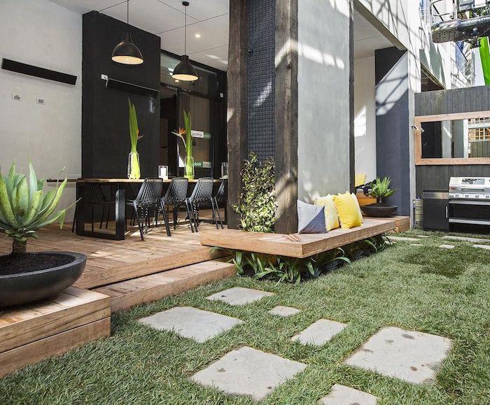 chemin de dalles de béton sur un gazon vert, terrasse bois avec table et chaises bois et metal, suspensions industrielles, banc bois autour d une colonne