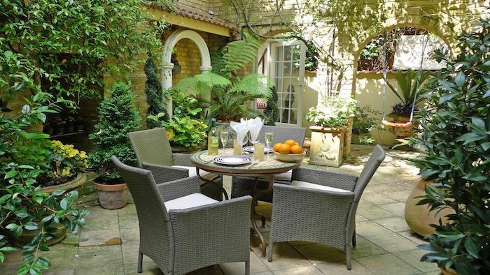 dalles de béton, chaises tressées, table ronde, plantes vertes dans gros pots de fleurs, maison vintage de campagne